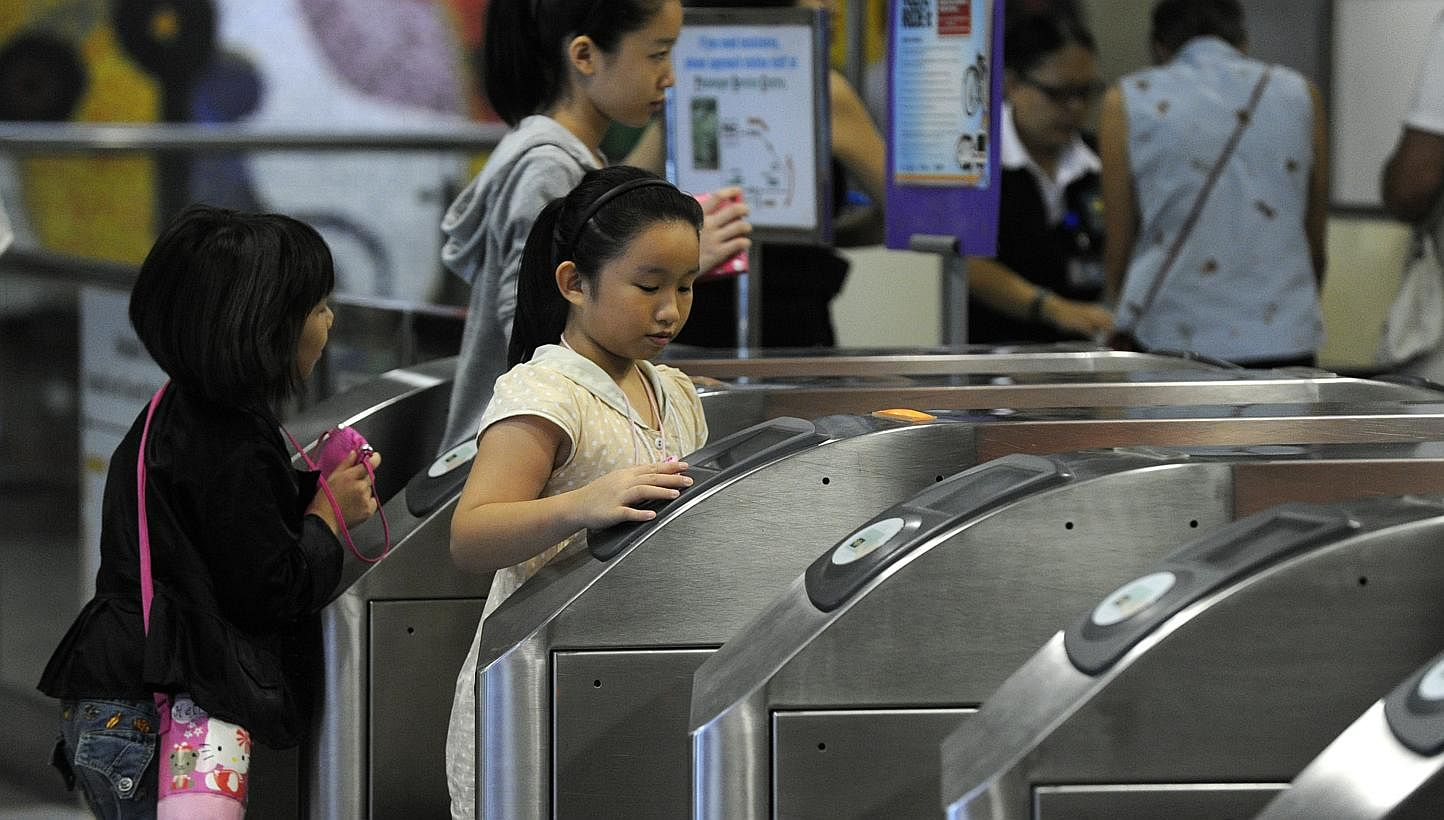 Commuters tapping their EZ-Link cards on the fare gates at Dhoby Ghaut MRT station in 2012. From today till Dec 31, commuters with cards that expire this year - regardless of whether they have been used recently - can get them replaced at any Transit