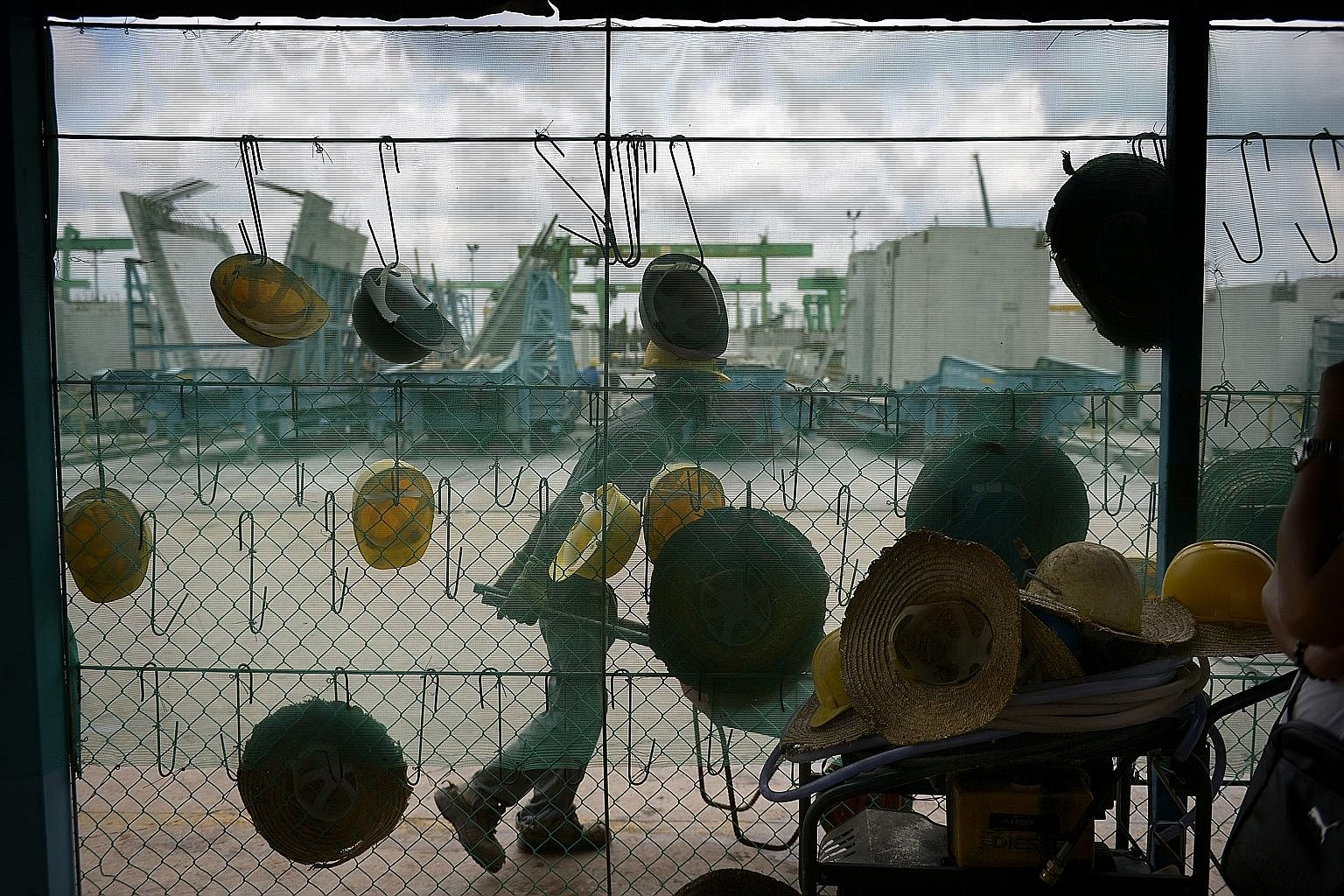 Workers' safety helmets hanging outside the canteen in the Sunway Concrete precast plant in Tampines. An army of workers work almost daily to churn out tonnes of precast building components for construction sites islandwide.