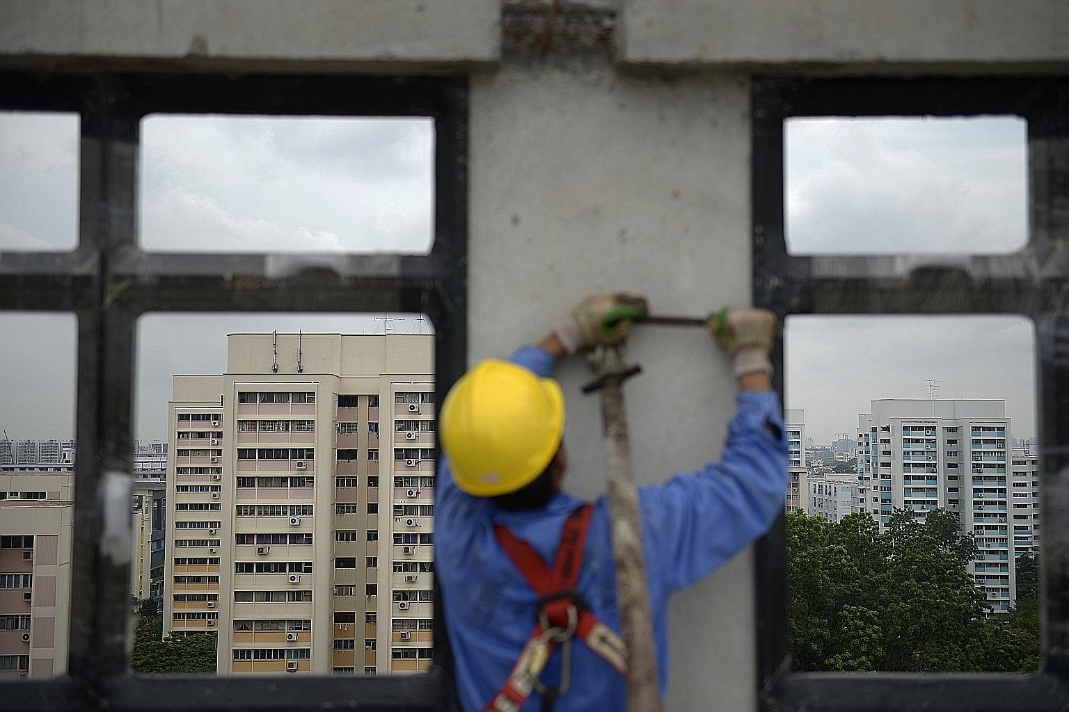 A worker tightening a brace bolted to a facade that had just been lifted into position in a Hougang Crimson block. The brace stays on until the adjoining walls and beams are put in place.