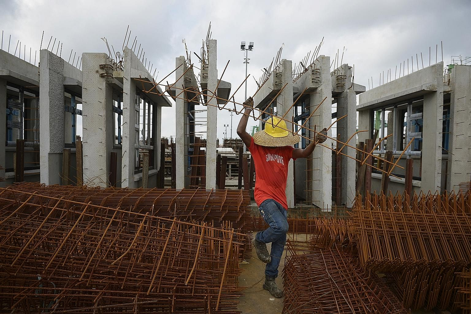 "A worker sorting out reinforcing steel bars, known as ""rebars"". In the background are HDB facades that are waiting to be delivered to the worksite."