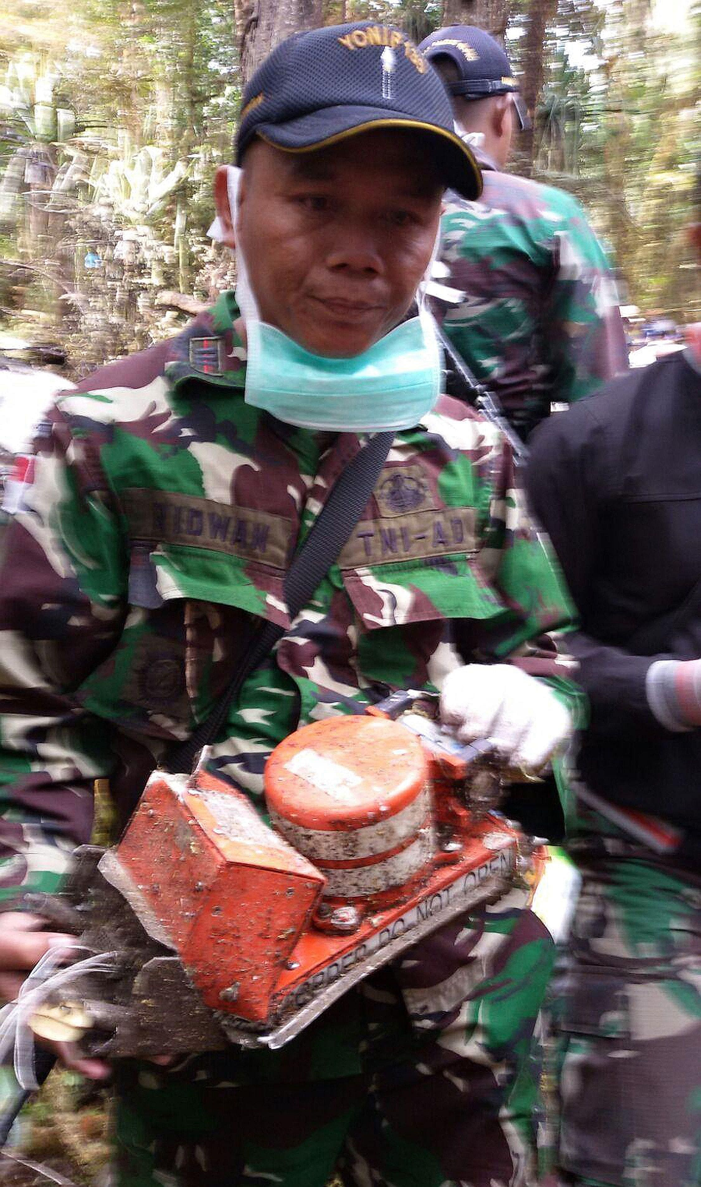 A soldier holding a recovered black box flight data recorder from the Trigana Air plane that crashed in eastern Indonesia on Sunday. All 54 people on the flight perished.