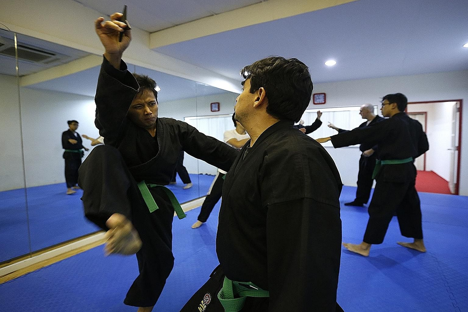 (Above) Ninjutsu student Lal Rin Lian uses a shuriken to distract his opponent - a common tactic that seeks to buy a practitioner sufficient time to take out his attacker - as he delivers a surprise kick during training. Besides striking, grappling,