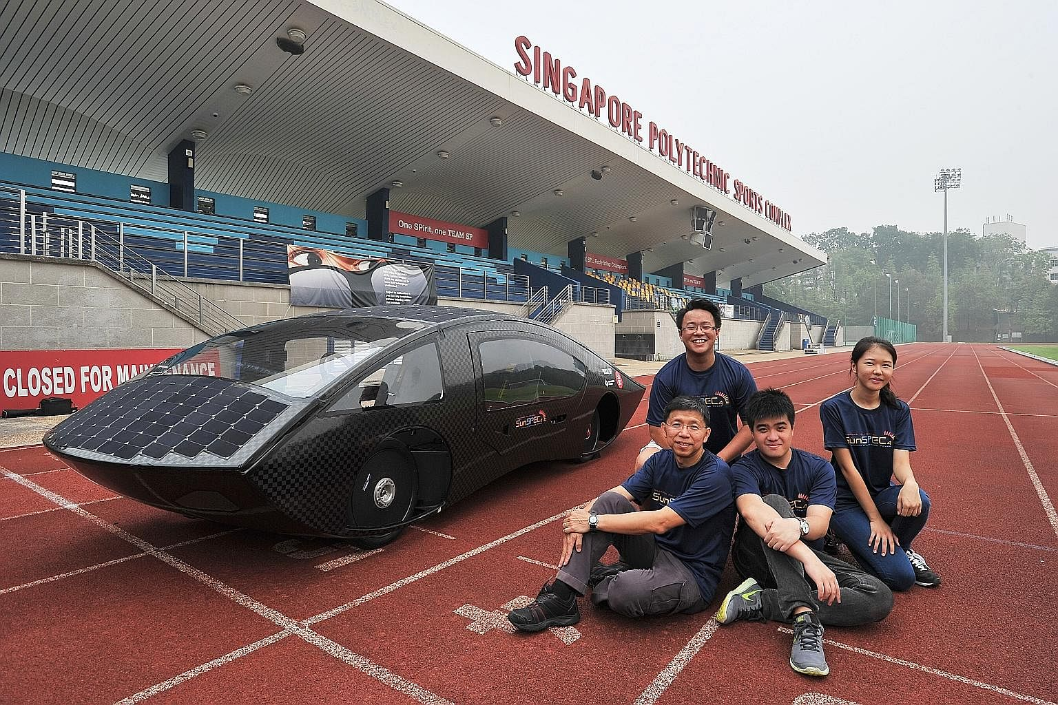 (Clockwise from bottom left) Team manager and senior lecturer Steven Chew with students Daniel Quick, 20; Lee Sunho, 21; and Cheong Yong Quan, 21, who are driving the Singapore Polytechnic team's black SunSPEC4, a 220kg carbon-fibre car lined with so