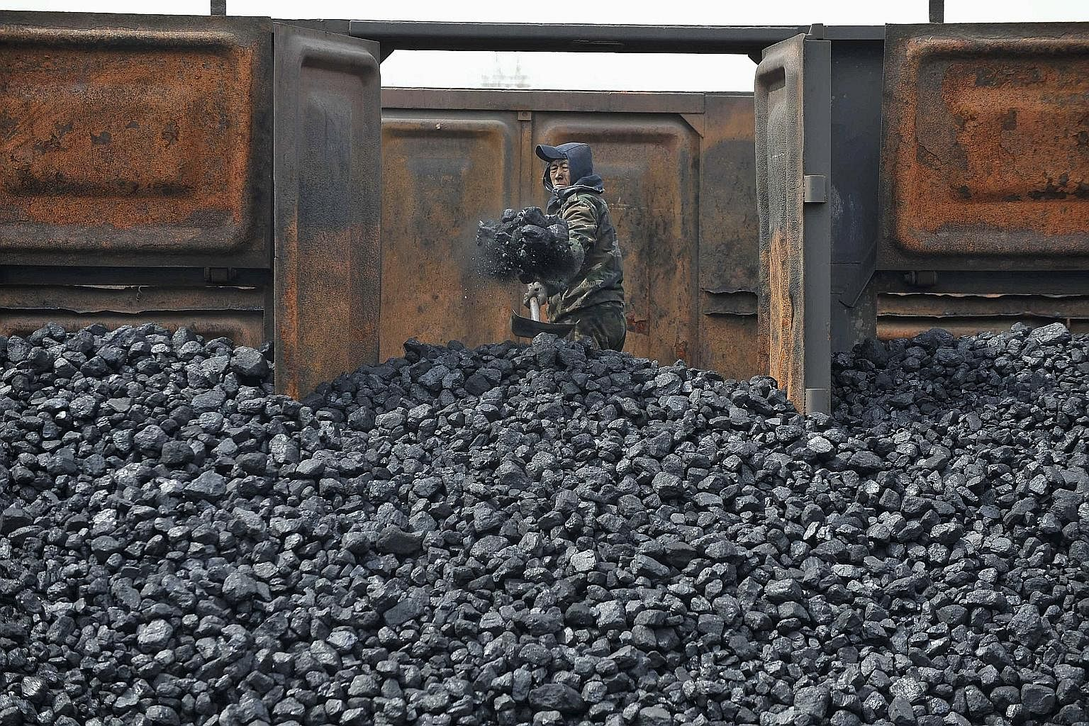 A worker unloading coal at a storage site along a railway station in Shenyang, Liaoning province, in China. Faced with choking air pollution, China is starting to shift away from coal-fired power plants and is also forcing dirty industries to clean u