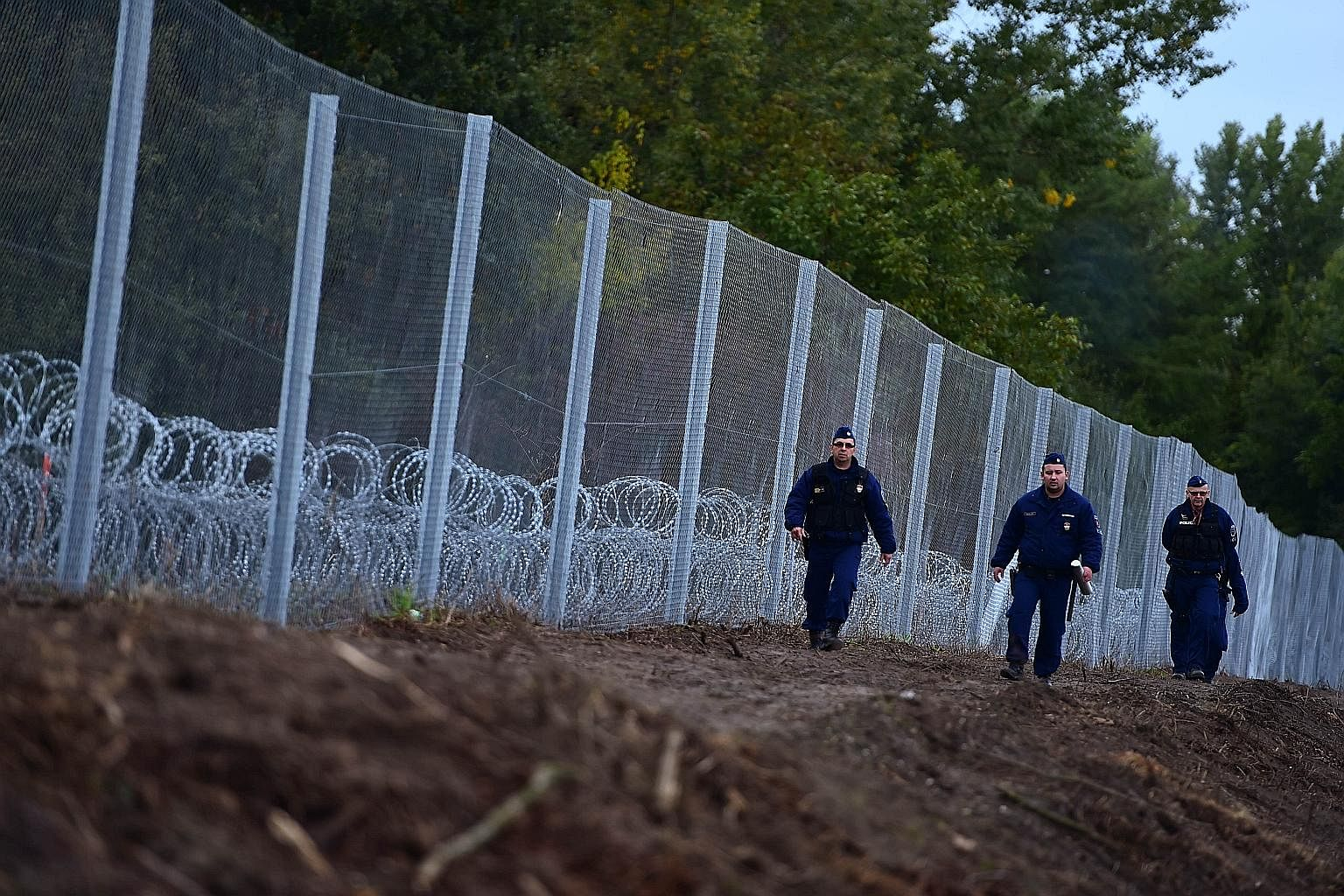 Police officers patrolling a newly erected fence at the Hungarian- Croatian border near Zakany. As governments erect barriers and reinstate border controls, the refugee crisis is disrupting flows of people and gumming up trade.