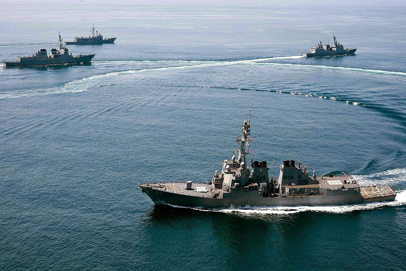 A handout photo released by the US Navy dated May 25 of the guided-missile destroyer USS Lassen (foreground) conducting a trilateral naval exercise with the Turkish and South Korean navies.