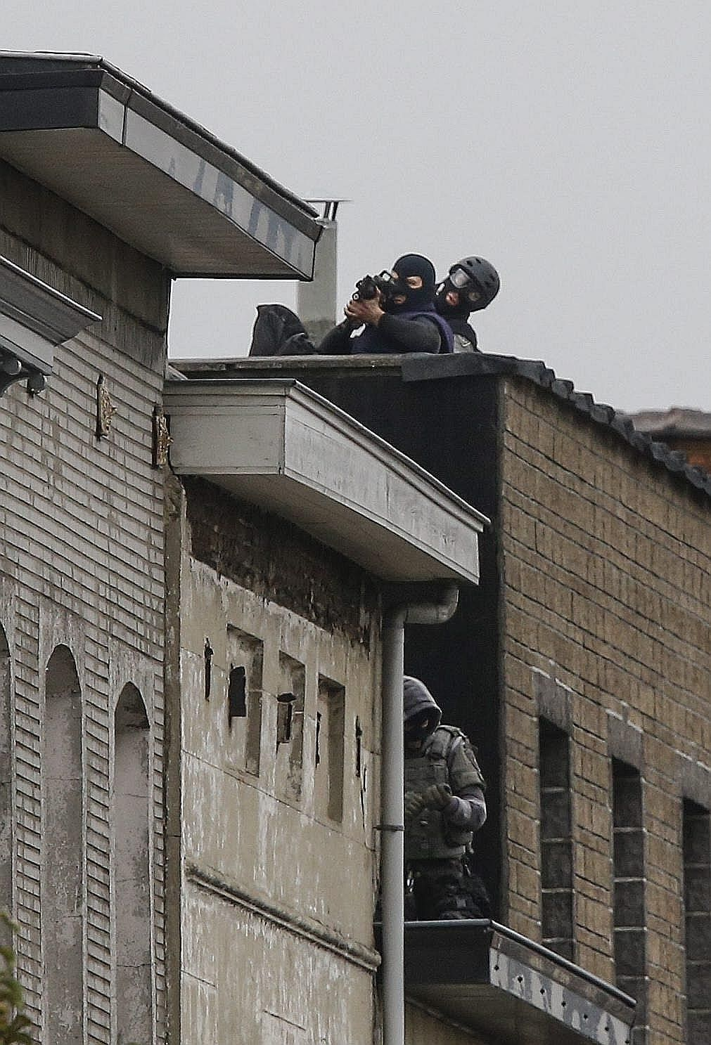 Snipers in Rue Delaunoy in Molenbeek in Brussels, Belgium, yesterday, where the manhunt for the terror suspects has widened to.