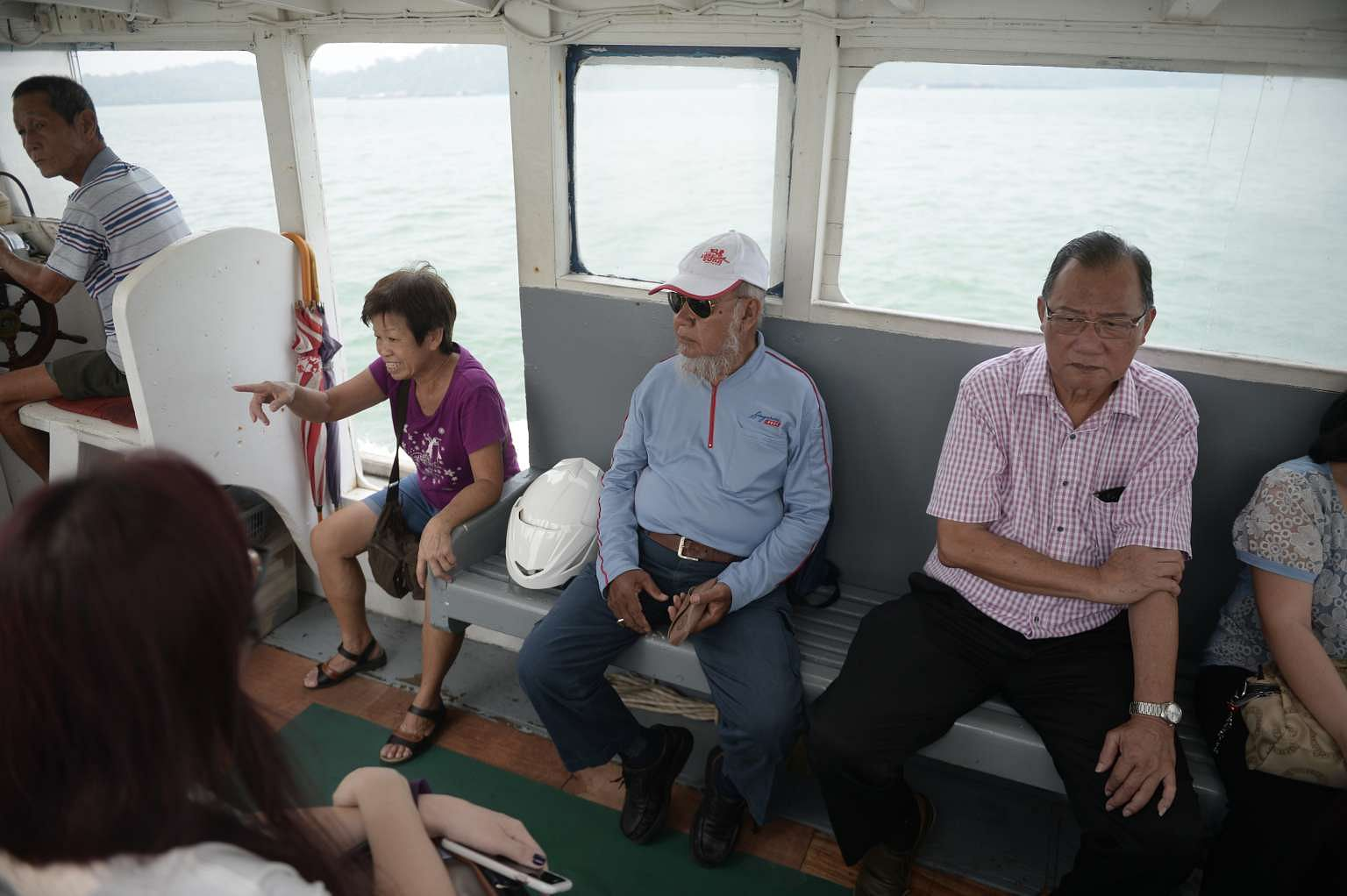 Mr Haron Jomahat (centre) takes a boat five days a week to Pulau Ubin, where he delivers mail to about 50 buildings.