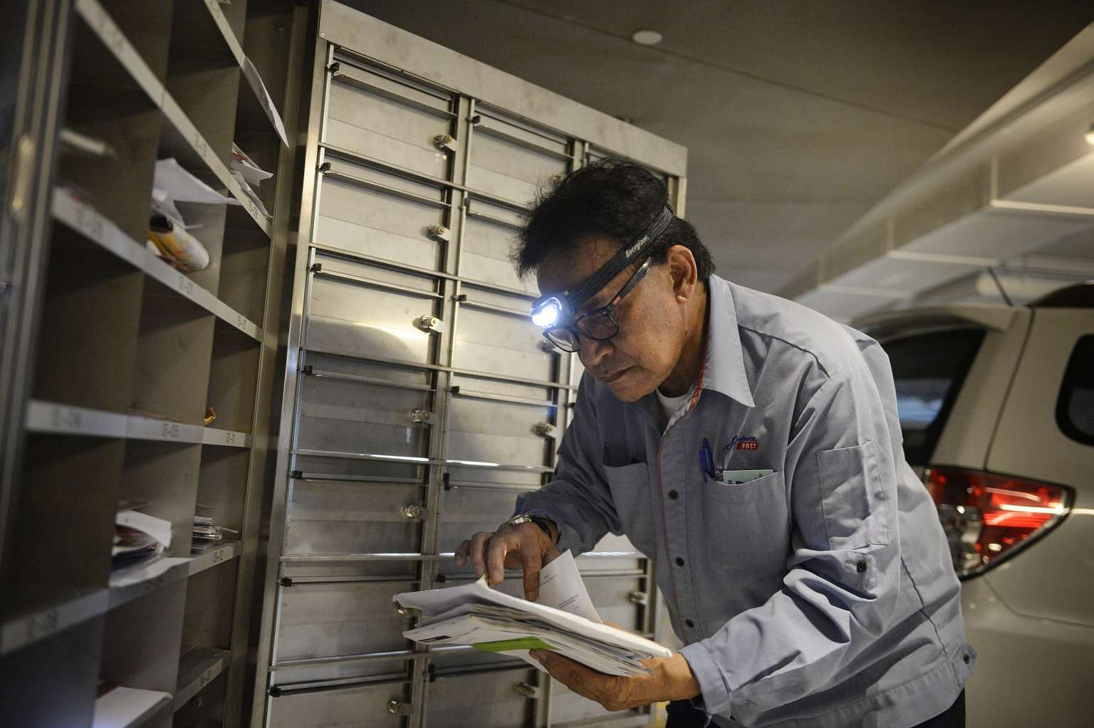 Postman Salim Nahrawi, 69, delivering letters at a building in Tanjong Pagar. The head light helps improve visibility.