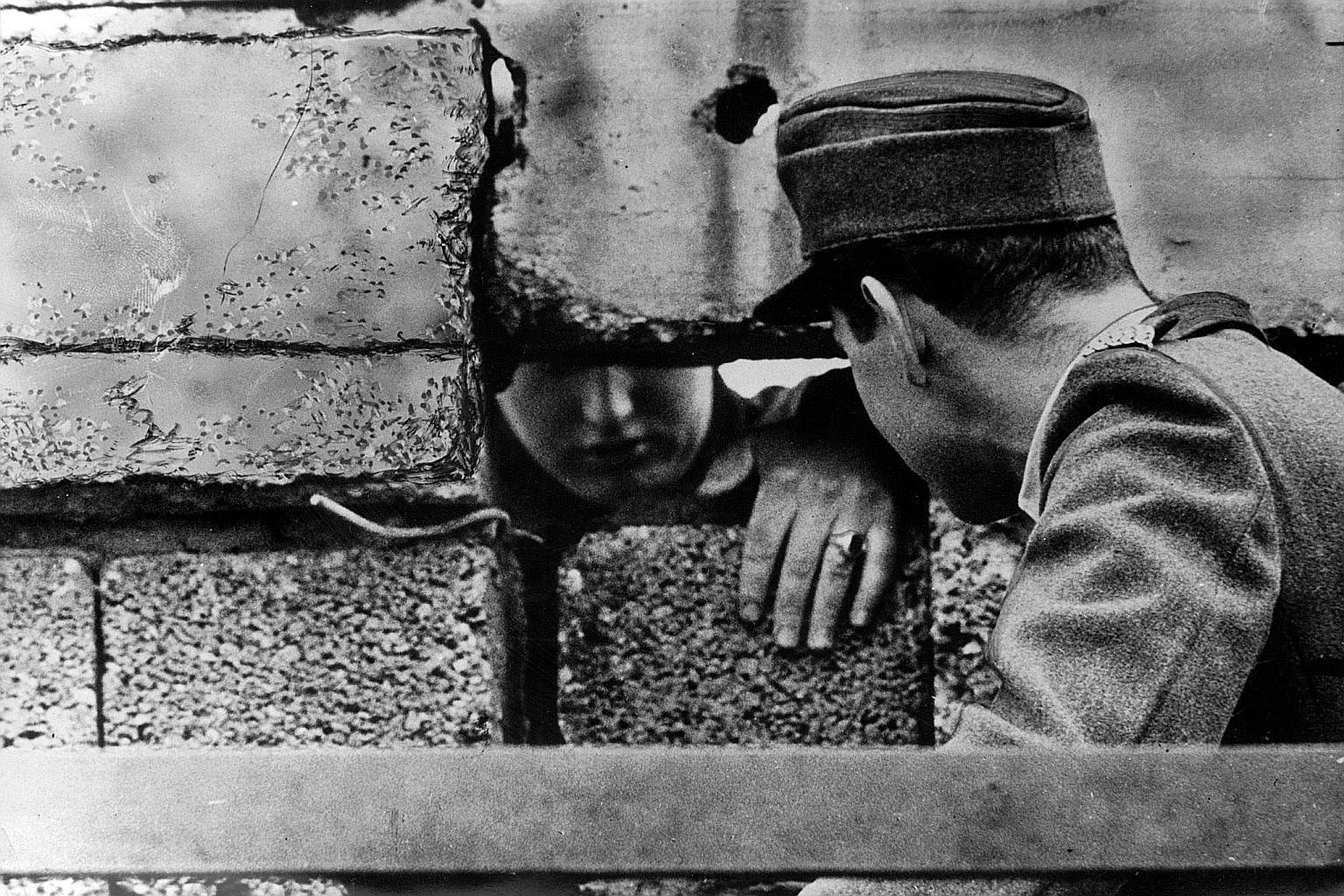 This image of the turbulent Konfrontasi period was captured in 1965 by veteran cameraman Willie Phua. Two German policemen communicating through a gap in the Berlin Wall, which was built by the communists in 1961. The spread of communism was one of t