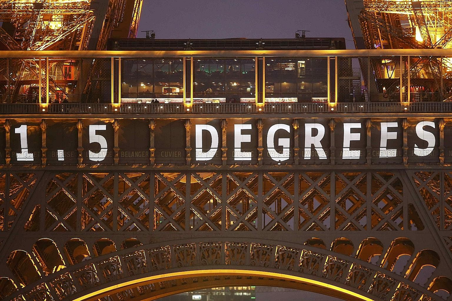 """The climate deal target of """"1.5 degrees"""" is projected on the Eiffel Tower. It refers to the aim of all participating nations to pursue efforts to limit global temperature increase to 1.5 deg C above pre-industrial levels."""