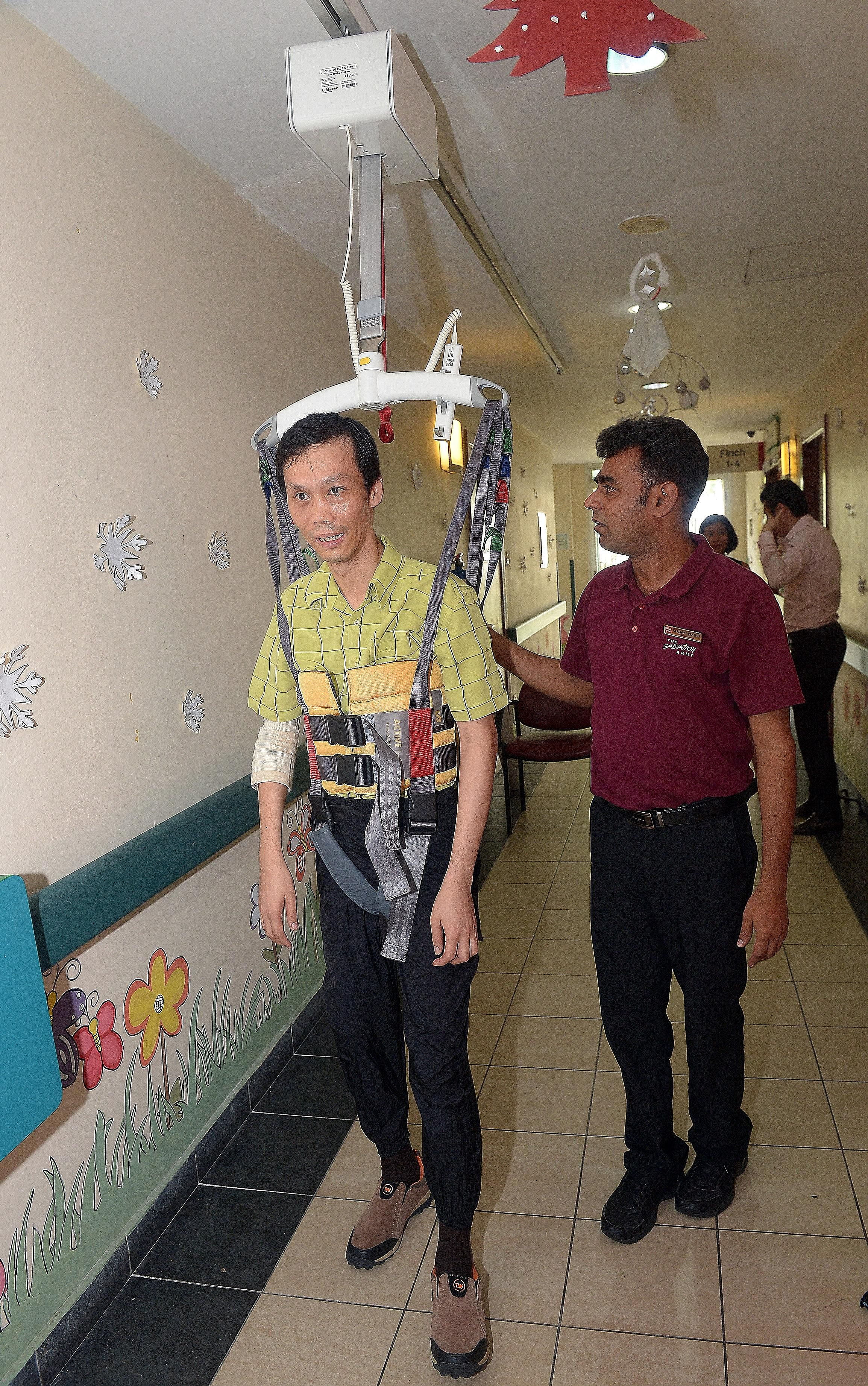 Senior physiotherapist Gladwin Prabhu, 39, helping along client Chang Phan Yong, 41, who is strapped into a newly installed ceiling hoist at The Salvation Army's Peacehaven Nursing Home, yesterday. Funds for the $10,000 hoist were donated by Nippon P