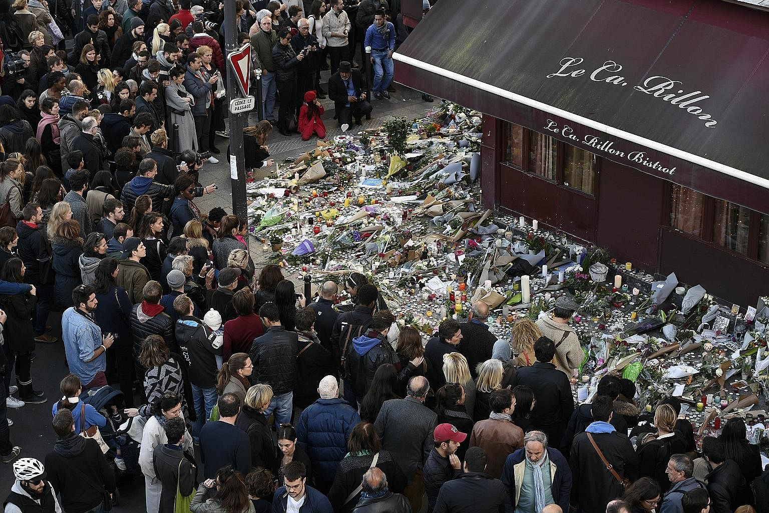 People gathering on Nov 16 for a memorial at a restaurant attacked by gunmen days earlier, in Paris.