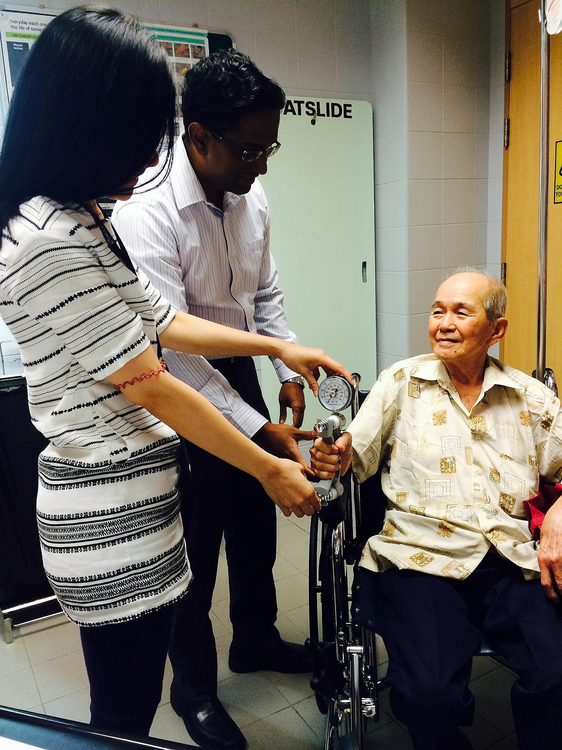 Dr Ravindran Kanesvaran and clinical coordinator Ong Zi Ling testing an elderly cancer patient's grip strength at the National Cancer Centre Singapore.