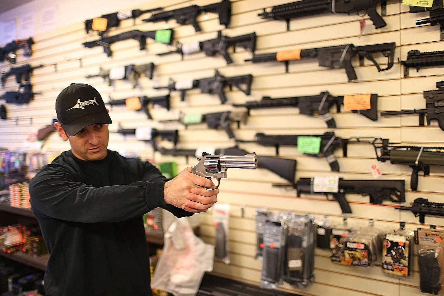 An employee demonstrating the use of a handgun at a firearms store in the US. On the question of whether more guns create more safety or more risk, the evidence is clear that most gun owners use firearms responsibly, but, with more guns, there are mo
