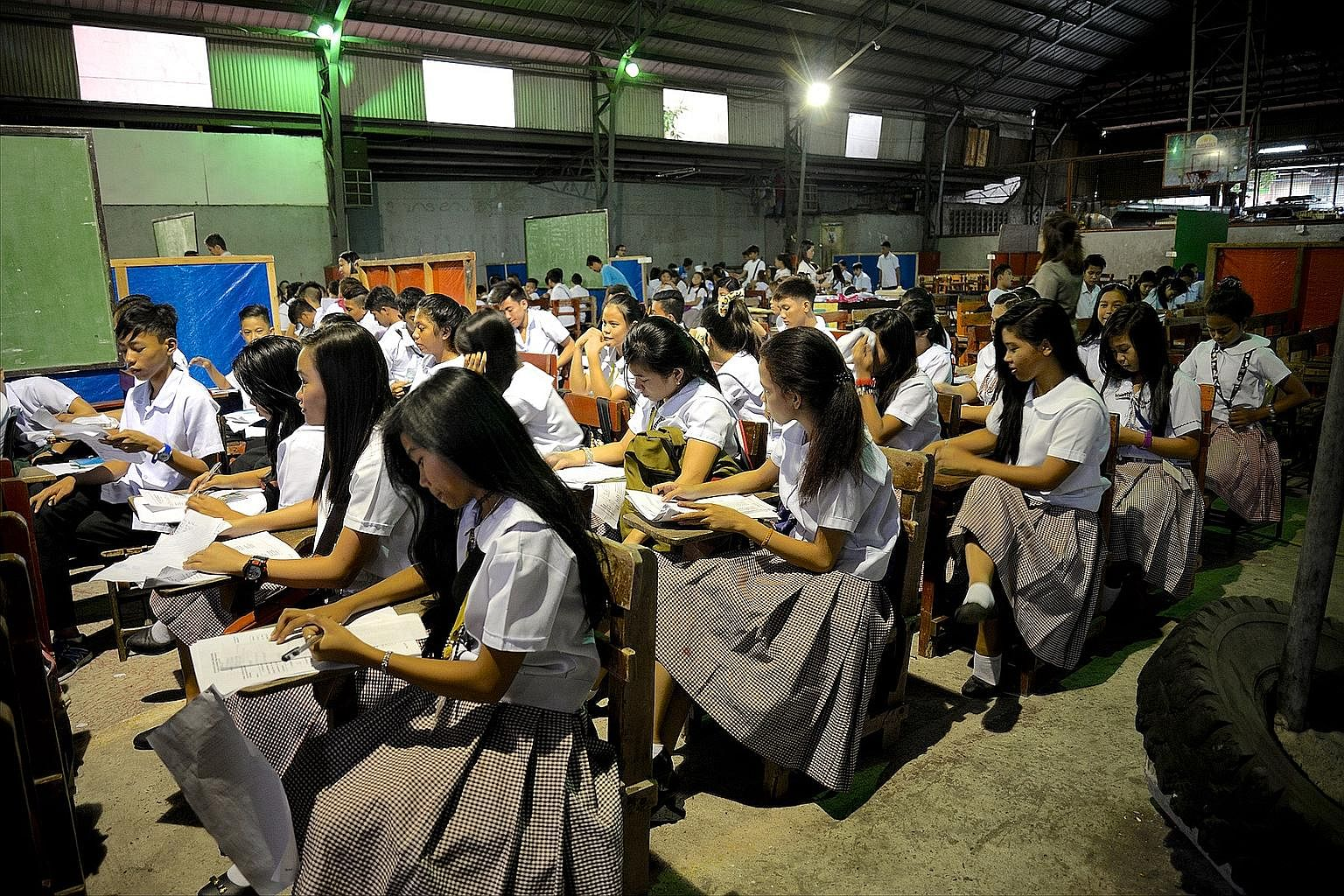Students at the San Rafael Technological School in Navotas city, just an hour north of Manila, having classes inside a gymnasium. A new school building is being constructed that will give the 1,008 students 16 classrooms, double what they had before.