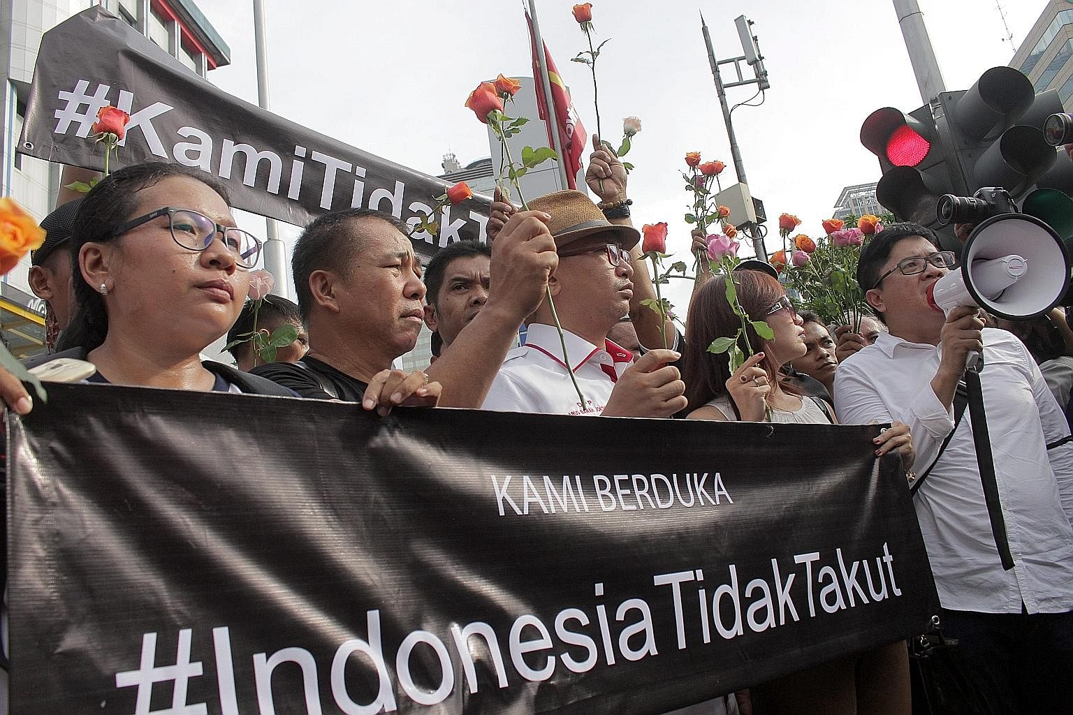 "Activists holding a banner last Friday that said ""Indonesia is not afraid"" at the site of a bombing in Jakarta. The day before, local militants had launched an assault in downtown Jakarta, which left seven dead."