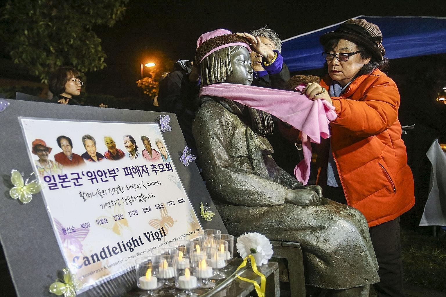 Supporters placing a scarf and a hat on a memorial statue honouring comfort women at Glendale Peace Monument in California during a candlelight vigil on Jan 5.