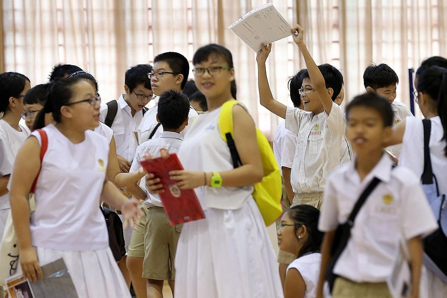 Pupils with their PSLE results. The MOE's stance on strictly adhering to cut-off points seems to go against the new direction of learning.