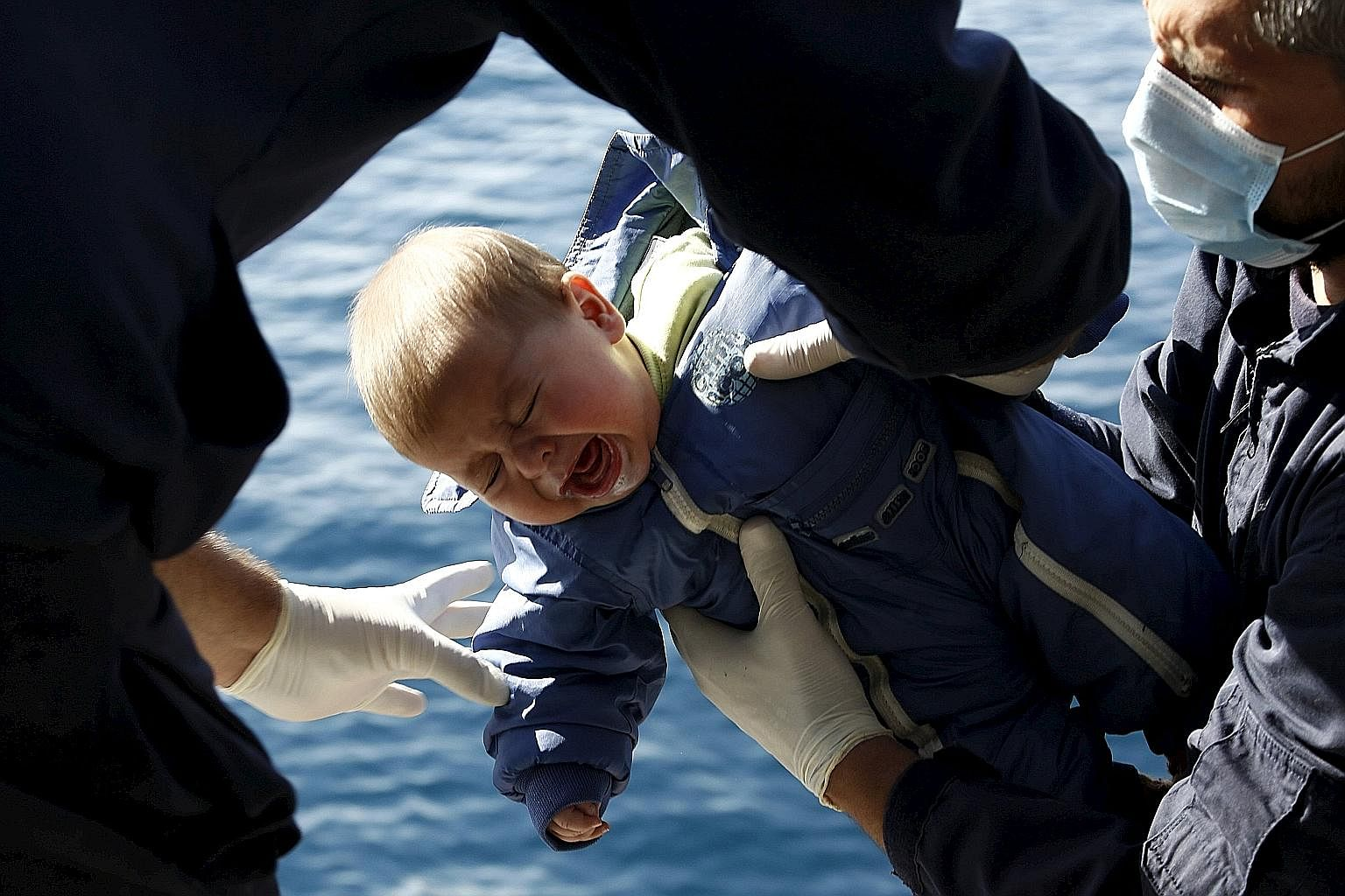 Greek Coast Guard officers transferring a baby to the safety of their vessel from a dinghy carrying refugees and migrants during a rescue operation in the open sea between the Turkish coast and the Greek island of Lesbos on Monday.