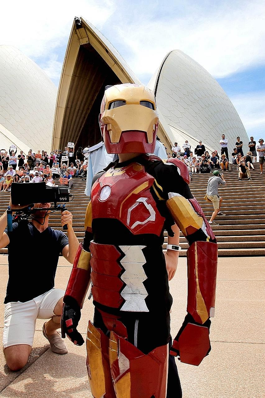 Australian Domenic Pace, 9, acting out a scene on the steps of the Sydney Opera House on Thursday, as he is granted his wish of becoming a superhero. Sydney police staged the elaborate event, with Hollywood star Robert Downey Jr, who has played Iron