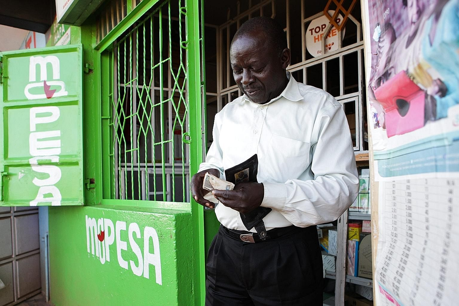 A Kenyan man counting his cash after making a withdrawal with his mobile phone at an M-Pesa outlet in Nairobi. M-Pesa is a mobile money transfer platform offered by mobile network operator Safaricom. Starting with payments, tech companies have moved