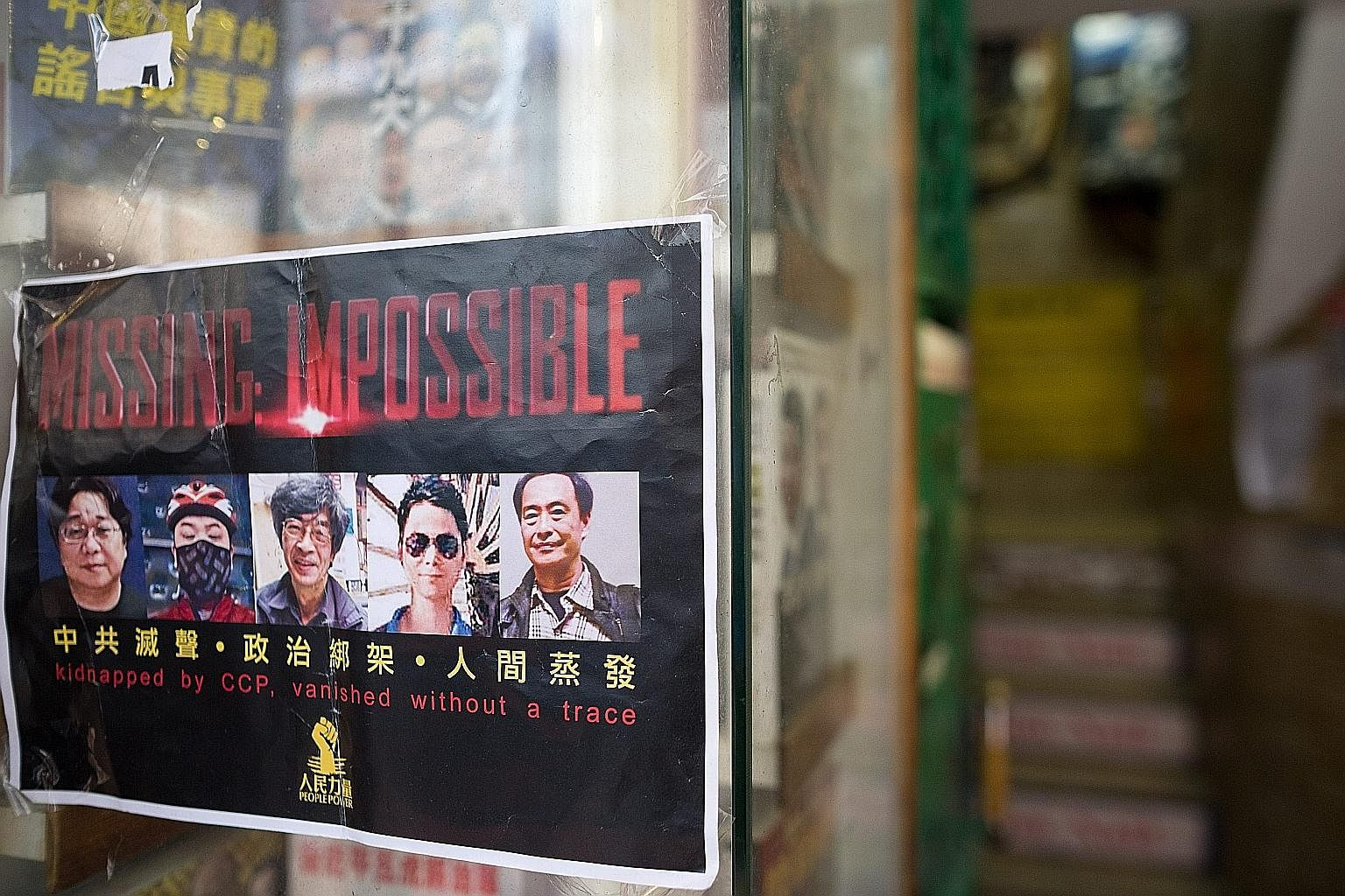 A flier with the photos of five book publishers and editors who went missing, at the entrance to a bookshop in Hong Kong.