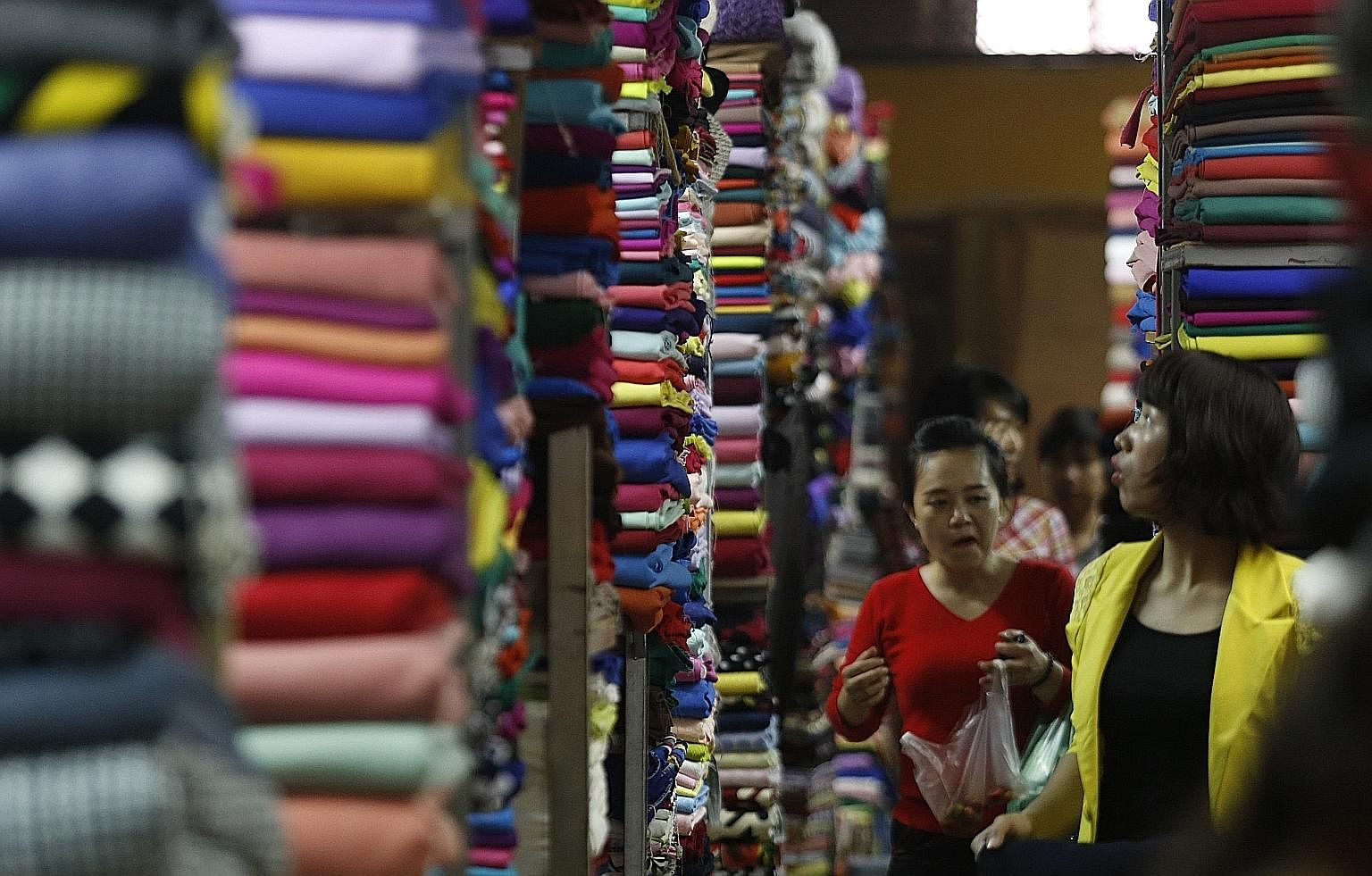 Customers walking among rows of fabric on display at a market in Hanoi. Despite Vietnam's tremendous progress, the nation remains in a fragile state with one-third of its 30 million people being vulnerable to falling back into poverty.