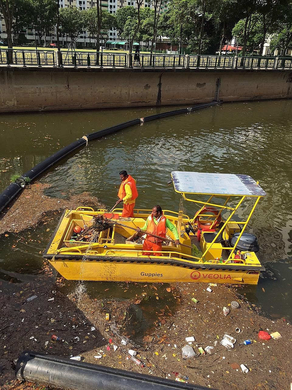 Workers cleaning up debris that was washed down Alexandra Canal, near Great World City, after a storm last month. Traps and float booms are placed at waterways to minimise litter flowing into the sea. Last year, the NEA collected about 920 tonnes of