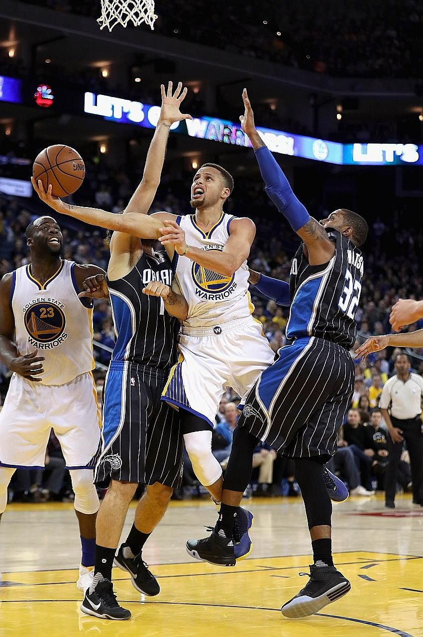 Stephen Curry of the Golden State Warriors (second from right) shoots after evading close marking from C. J. Watson (32) and Evan Fournier of the Orlando Magic on Monday. The Warriors won 119-113 to overtake the Chicago Bulls' record of 44 straight h