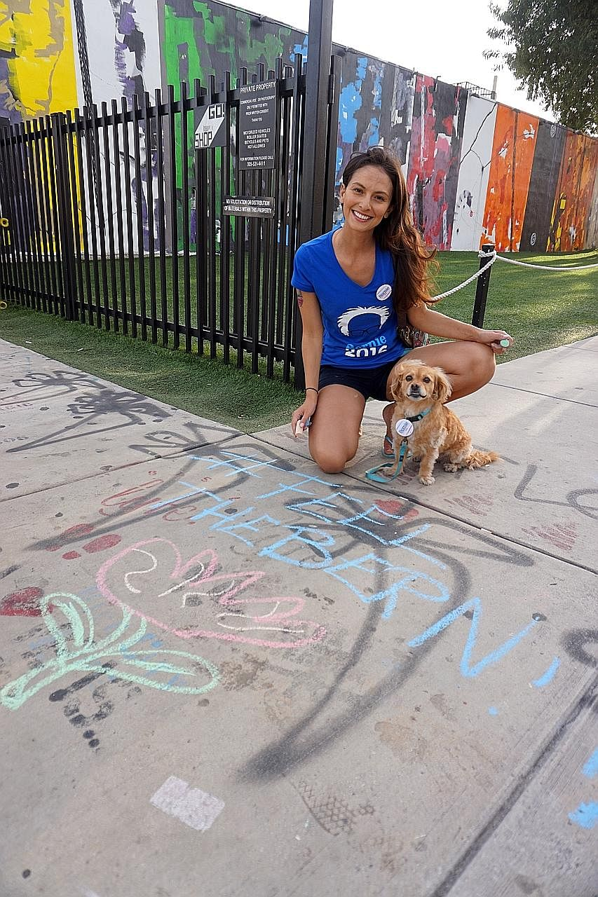 """Actress Candice Loper Marisol, 33, chalking the pavement in support of Mr Bernie Sanders. She said she is tired of """"corporate welfare that is going to big banks and companies""""."""