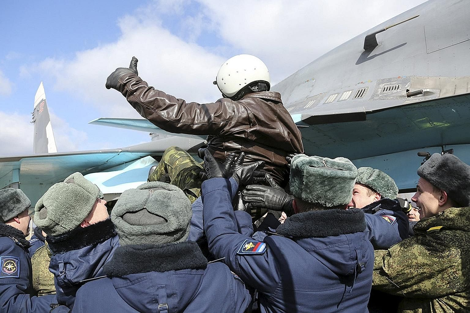 A Russian military pilot being greeted upon his return from Syria to a home airbase on Tuesday. Although President Putin has announced the withdrawal of troops from Syria, where Russian forces have been pounding rebels who are against President Assad