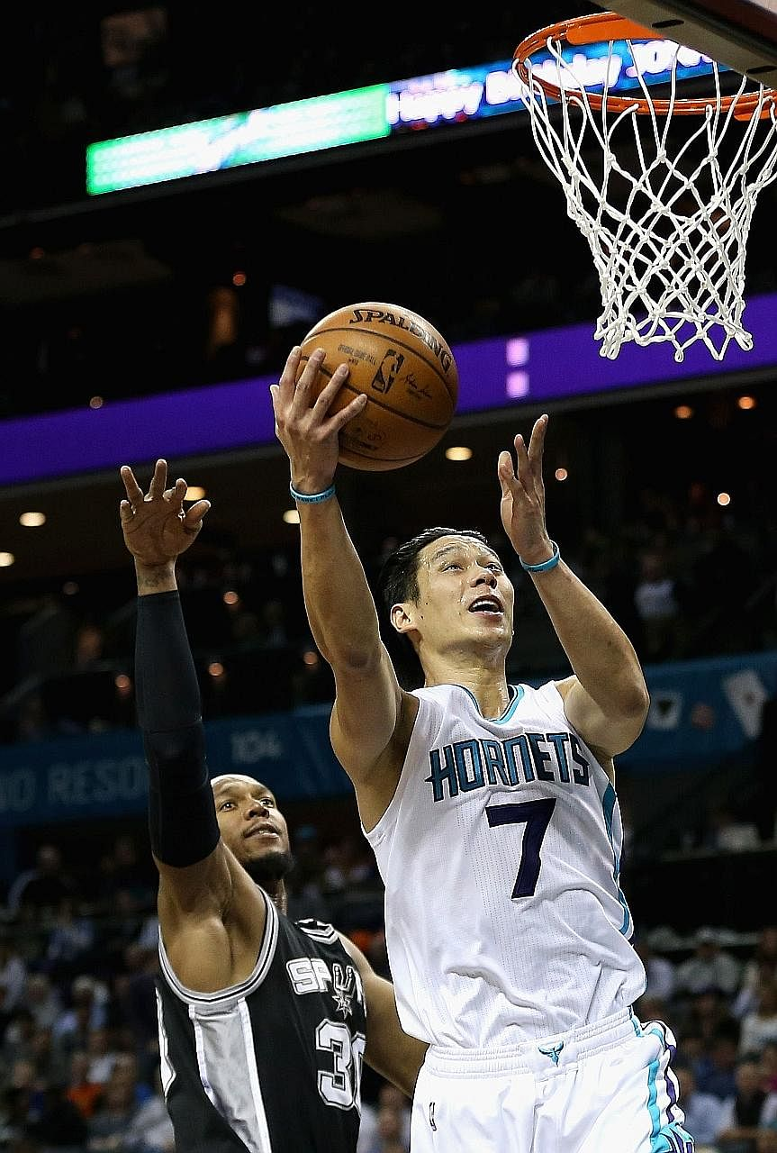 Charlotte's Jeremy Lin driving to the basket against San Antonio's David West at Time Warner Cable Arena. Lin scored 29 points, including four three-pointers, as the Hornets defeated the Spurs 91-88.