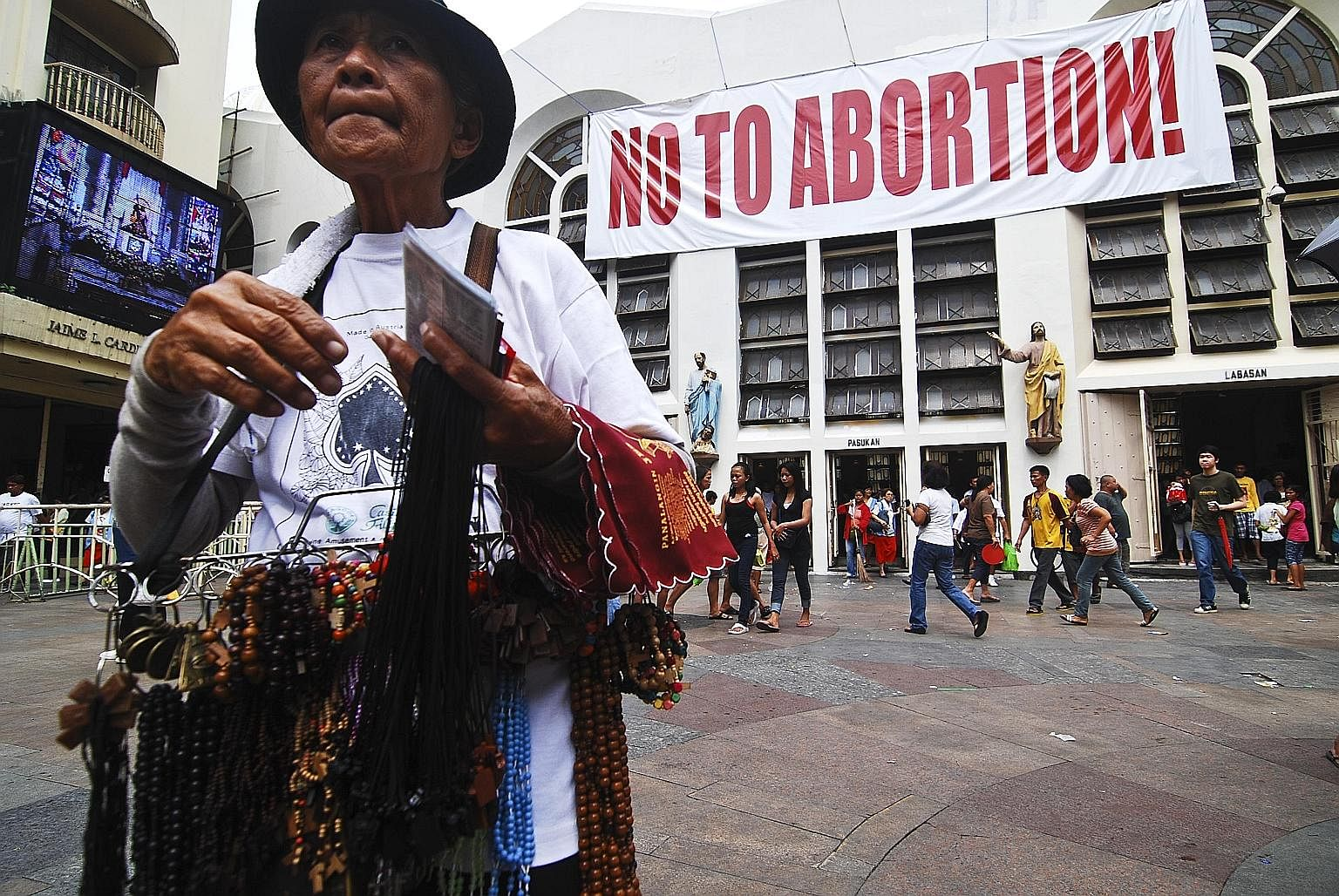 """An anti-abortion sign on the wall of the Minor Basilica of the Black Nazarene in Quiapo, Manila. Vendors outside the church sell a dizzying range of goods, including the banned anti-ulcer drug Cytotec, known to induce miscarriage. That the """"abortion"""