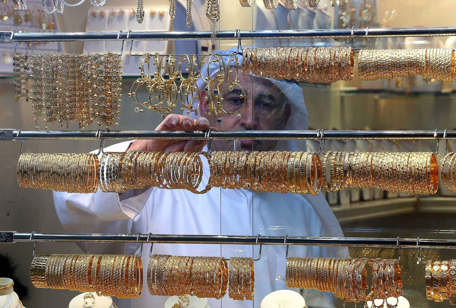 A Palestinian woman shopping for gold on March 30. Gold prices feast on economic uncertainty, and this year's buffet of market woes fattened the yellow metal up to recent highs.