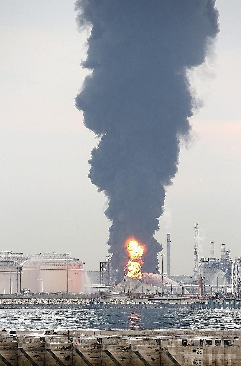 Smoke billowing from the fire at a facility on Jurong Island, as seen from Tuas South at 6.18pm. The burning tank was contained within a protective wall, so that two other nearby tanks would not be affected.