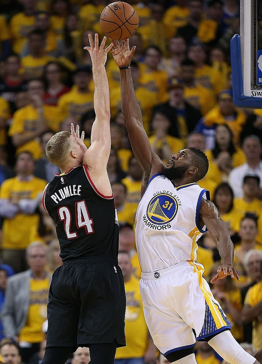 Festus Ezeli (right) of the Golden State Warriors blocking a shot by Mason Plumlee of the Portland Trail Blazers during Game 2 of the Western Conference semi-finals on Tuesday. Ezeli transformed an 11-point deficit into a 110-99 victory for the Warri