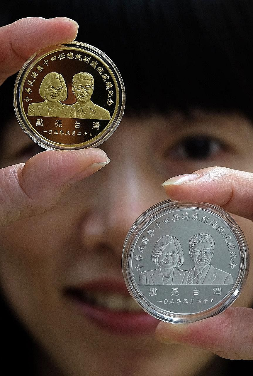 A woman displays gold and silver coins showing the portraits of incoming president Tsai Ing-wen and vice-president Chen Chien. Beijing has made clear its dislike for the pro-independence Ms Tsai.