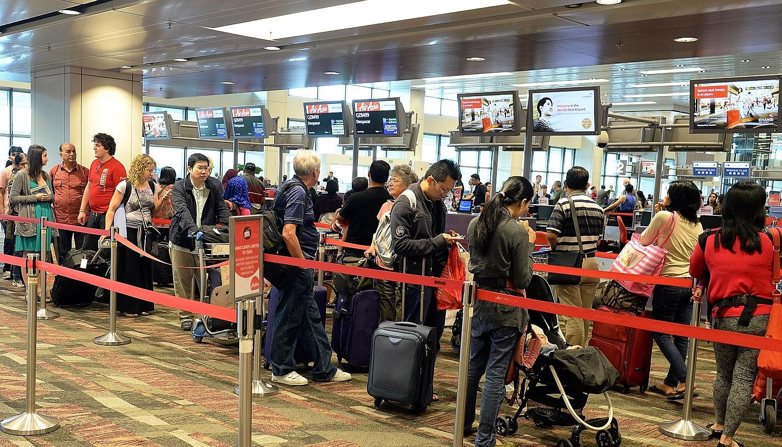Travellers at the AirAsia check-in counter at Changi Airport Terminal 1. Mr Wilson, the chief executive of Scoot, says the new alliance among eight low-cost carriers is a strategic move against other airline groupings. Three of the biggest budget air