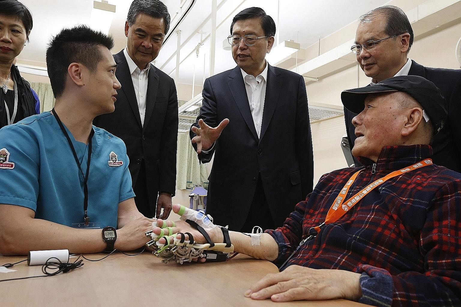 Mr Zhang (centre) speaking to a care provider at an aged care complex in Hong Kong yesterday. During his visit to the city, he attended 18 events, including meeting pan-democratic politicians.