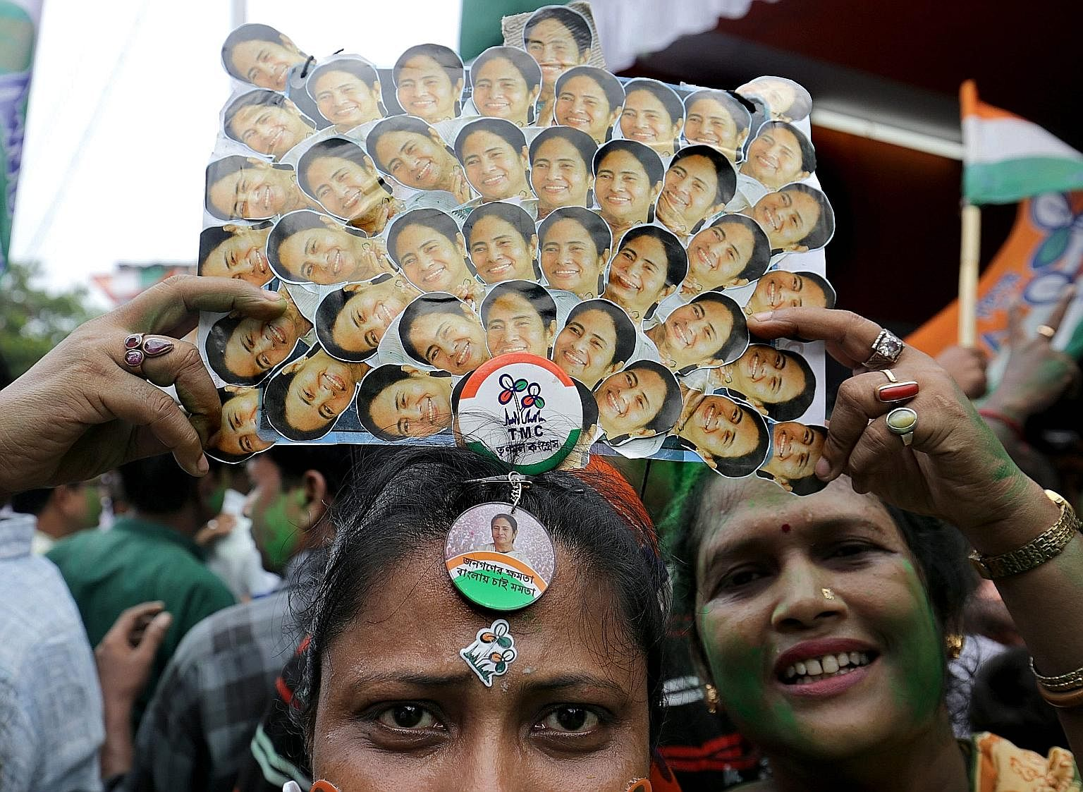 A Trinamool Congress party supporter wears a crown made out of Chief Minister Mamata Banerjee's photos during celebrations after she won an absolute majority in the West Bengal Assembly election in Kolkata.