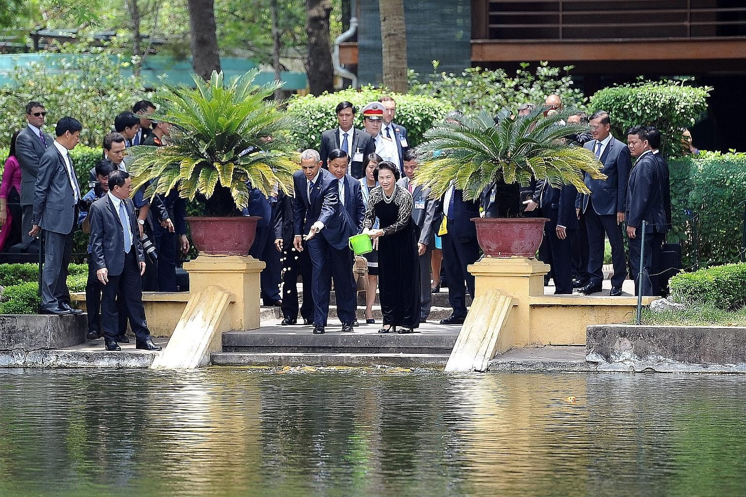 "Vietnamese people taking pictures as Mr Obama's motorcade drove past in Hanoi yesterday. The US leader's three-day trip to Vietnam is part of his administration's strategic ""rebalance"" to Asia. Mr Obama and Ms Nguyen Thi Kim Ngan, chairman of the Vie"