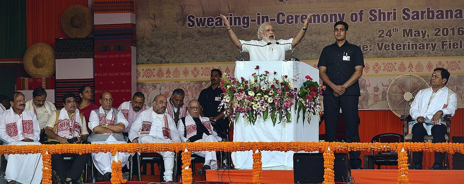 Mr Modi delivering a speech at the swearing-in ceremony for 10 ministers and Assam's new Chief Minister Sarbananda Sonowal (right) in Guwahati, Assam, on Tuesday.
