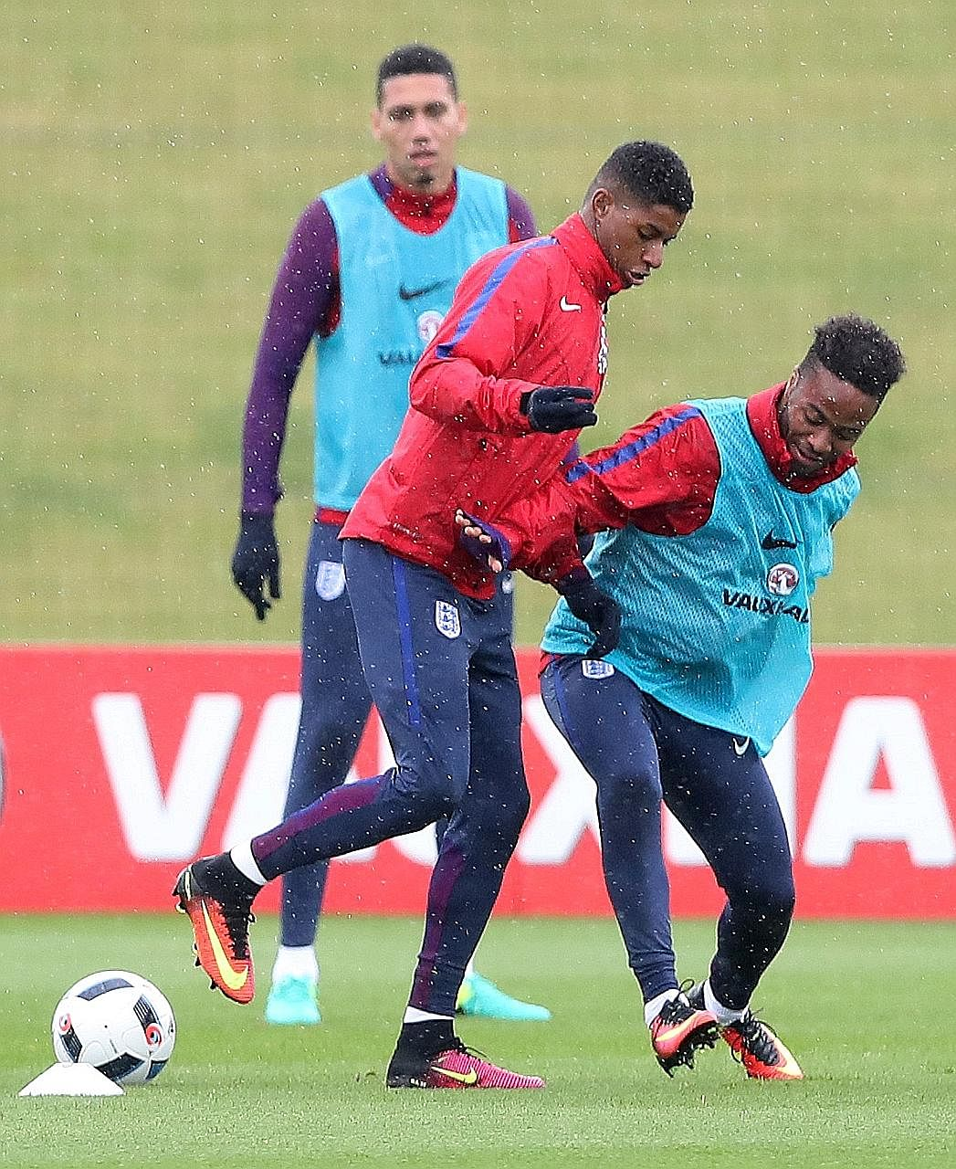 Marcus Rashford (centre) keeping the ball away from Raheem Sterling during England's training session as Chris Smalling watches on.