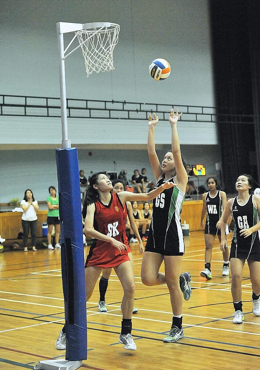 Raffles Institution goal shooter Isabelle Belanger (second from left) shoots as Hwa Chong Institution goal keeper Low Yixuan (left) defends at the Jurong East Sports Hall. Isabelle scored a game-high 50 points, single-handedly outscoring HCI.
