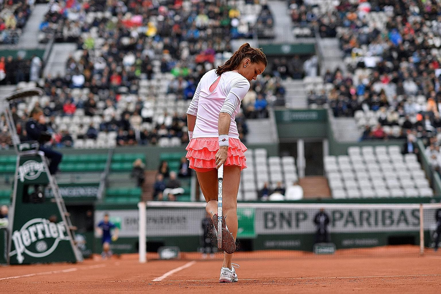 Agnieszka Radwanska removing clay from her shoes during her fourth-round match against Bulgaria's Tsvetana Pironkova at the French Open. But the Pole came unstuck, losing 6-2, 3-6, 3-6.