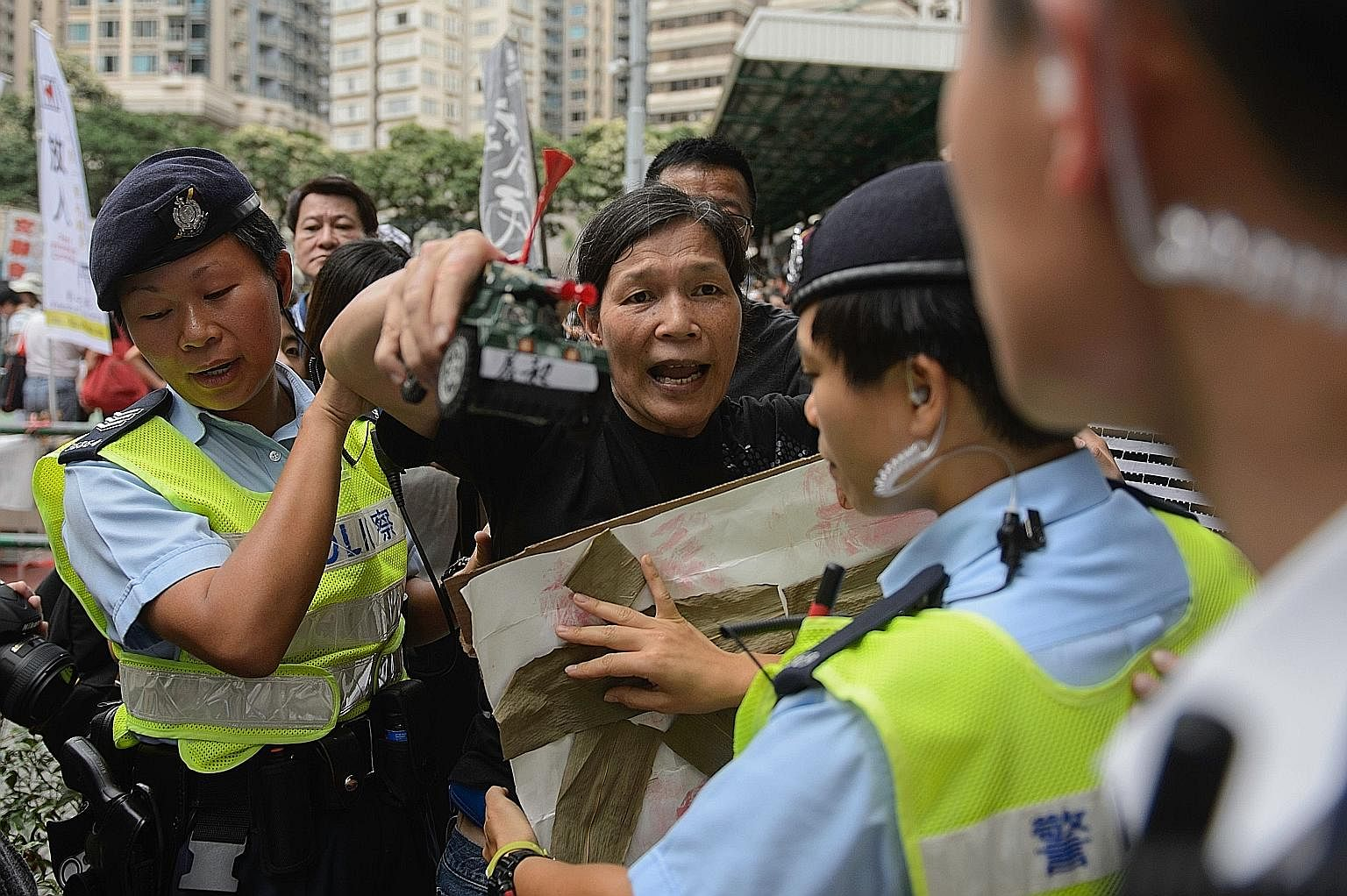 Police holding back a pro-democracy activist, with a toy tank in her hand, after she taunted pro-China demonstrators in Hong Kong on Sunday. The pro-China demonstrators had gathered to counter-protest against a pro-democracy rally ahead of the annive