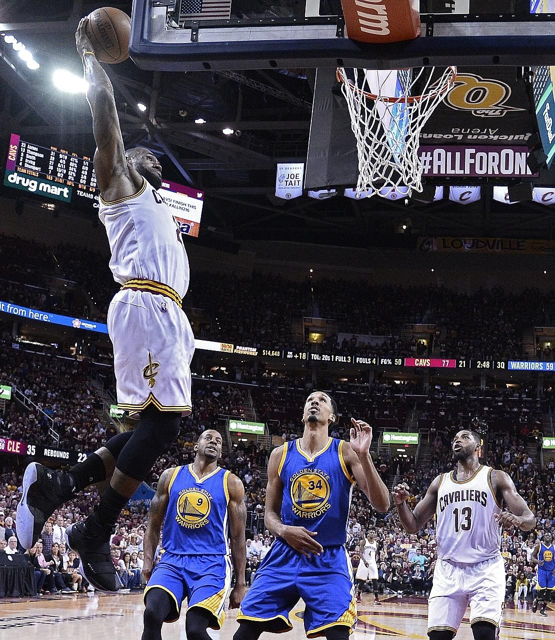 Cleveland's LeBron James dunks as Golden State's Andre Iguodala (centre) and Shaun Livingston look on. James set the tone for a 120-90 win to cut the Warriors' lead in the Finals to 2-1.