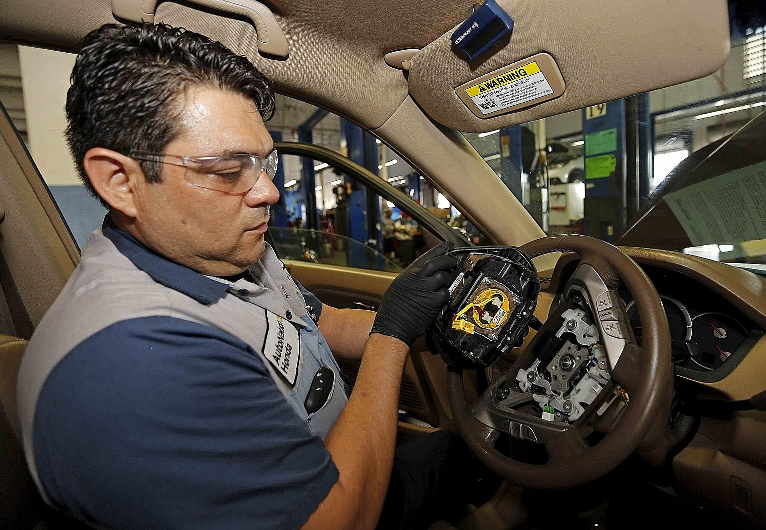 Technician Edward Bonilla holding a recalled Takata airbag inflator after removing it from a Honda car at a dealership service department in Miami, Florida.