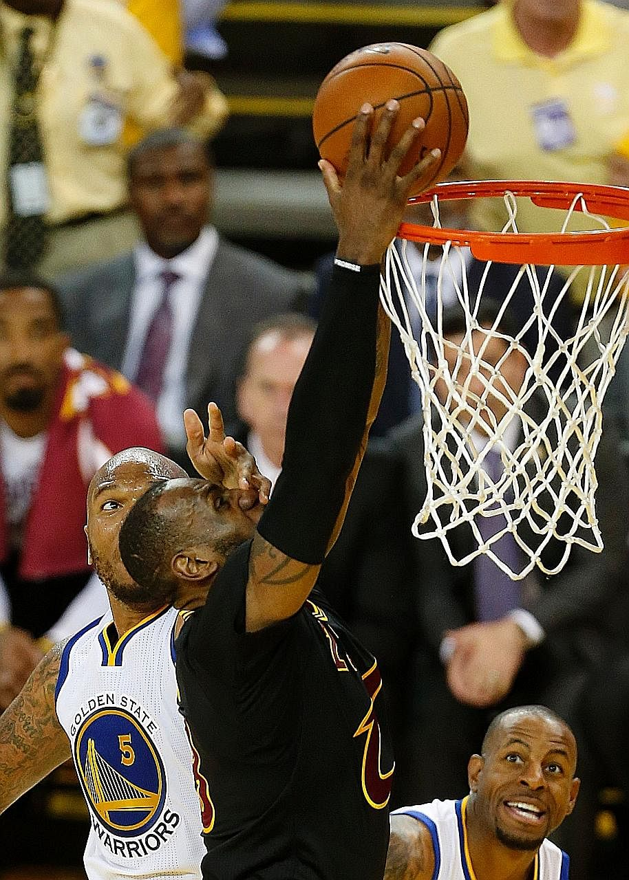 Cleveland Cavaliers forward LeBron James (right) scoring two of his 41 points against the Golden State Warriors on Monday. Team-mate Kyrie Irving also enjoyed a 41-point outing.